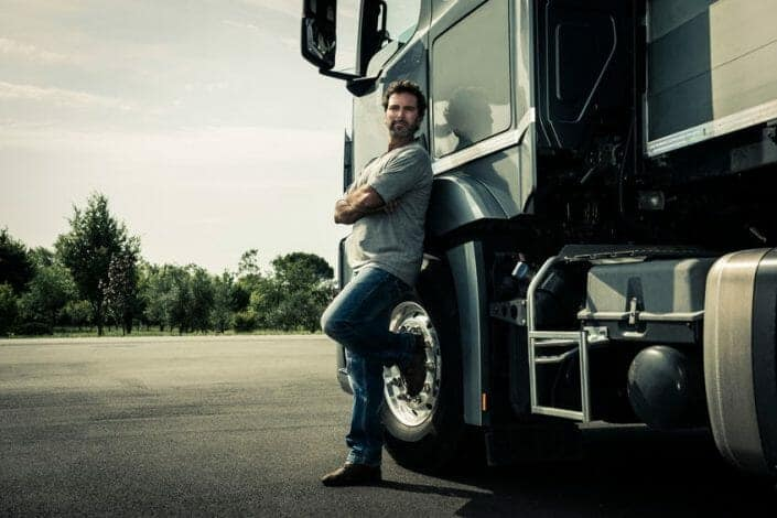 Truck Driver Leaning on his Truck Starting New Truck Driving Career