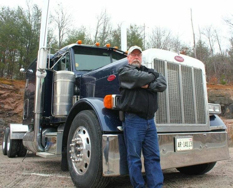 Experienced Veteran Truck Driver Smart Trucking Leaning on 379 Peterbilt