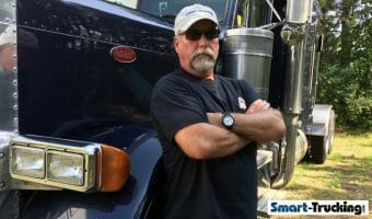 Truck Driver Standing Beside Blue Peterbilt