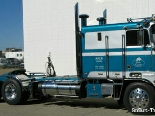 1984 blue white Kenworth Cabover Truck Parked Beside Building